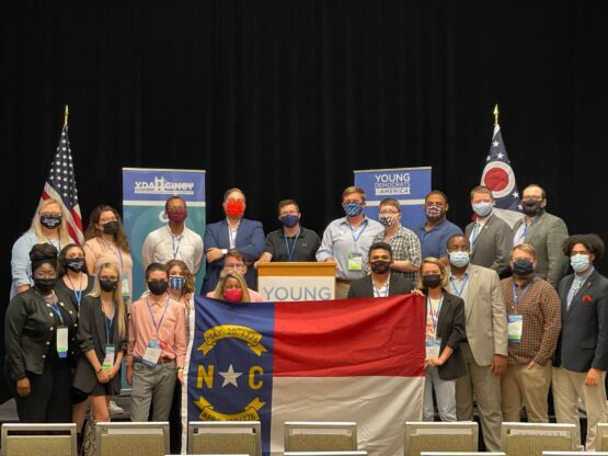 People standing on a stage wearing face masks, holding a North Carolina flag