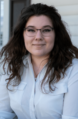A white, nonbinary person with long, brown hair and glasses in a white dress shirt.