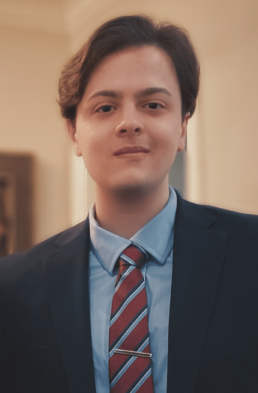 A white man with brown hair in a blue suit.
