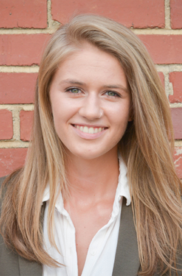 A white woman with long, blond hair and a small nose ring wearing a suit