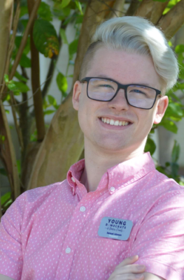 A white man with blond hair and glasses in a pink shirt