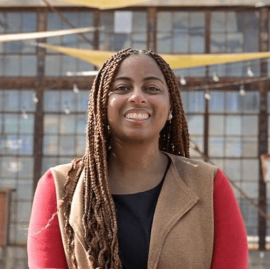A smiling black woman with long, brown hair in braids and a brown-and-red jacket over a black undershirt.