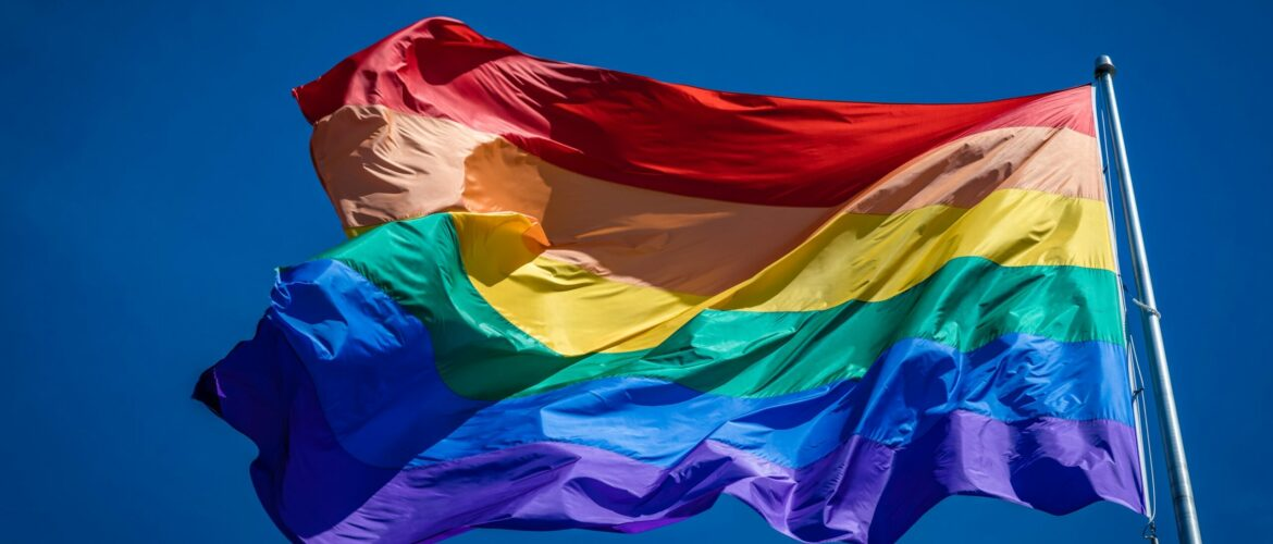 Close up of the enormous 20x30 foot rainbow flag flying proud over Harvey Milk Plaza in the Castro district of San Francisco California