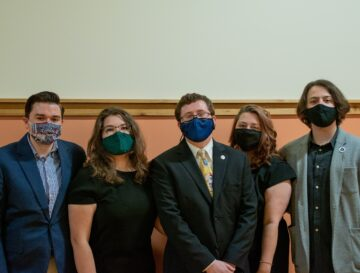 A group of five people in masks standing in a line.