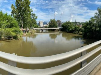 Panoramic view of a flooded river from a bridge with factories visible in the background