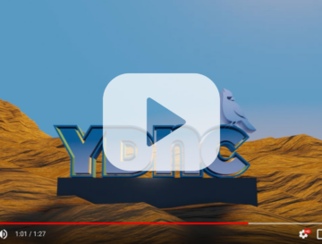 A screenshot of a YouTube video showing the YDNC Logo on a pedestal in a rocky landscape.